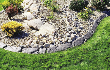 Closeup of a rock garden bed and lawn separated by landscape curbing